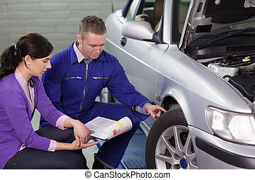 Mechanic showing the car wheel to a woman