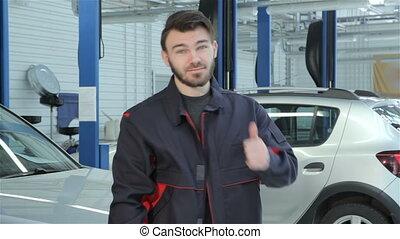 Mechanic shows his thumb at the car service