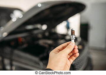 Mechanic shows spark plugs of the vehicle