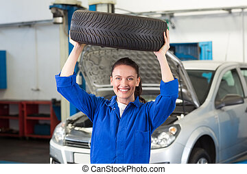 Mechanic smiling at the camera holding tire