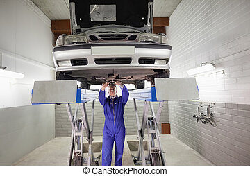 Mechanic standing while repairing a car with tools in a...