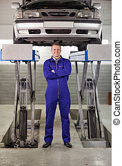 Mechanic standing with arms crossed below a car in a garage