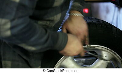Mechanic - At the station of the service being tested tire...