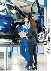 Mechanic talking to car owner