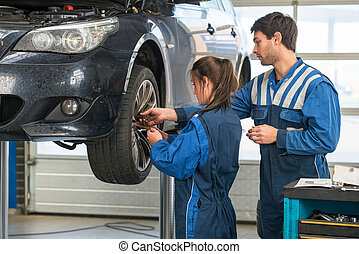 Mechanic teaching an intern in a garage - Mechanic teaching...