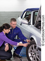 Mechanic touching the car wheel next to a woman in a garage