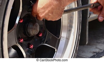 mechanic twists the nuts on the wheel