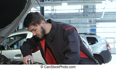 Mechanic twists wrench under car hood  at the car service