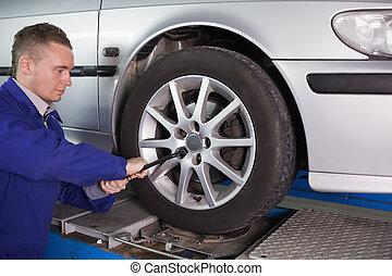 Mechanic unscrewing a bolt in a garage