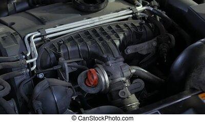Mechanic unscrews car part engine service