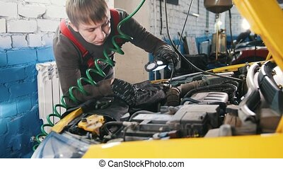 Mechanic unscrews detail of car in hood - automobile service...