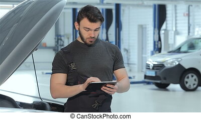 Mechanic uses a tablet at the car service
