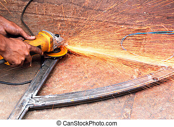 Mechanic using a electrically operated sawing machine to smooth the rough edges of a welded iron bar and sparks flying out because of extreme friction between the machine and the metal