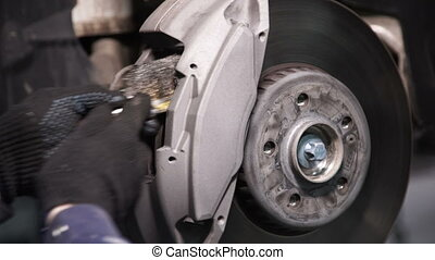 Mechanic using a wire brush cleans the place for car brake pads.