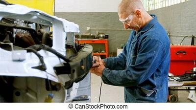 Mechanic using grinding machine on a car 4k - Mechanic using...