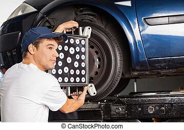 Mechanic Using Wheel Aligner On Car At Garage