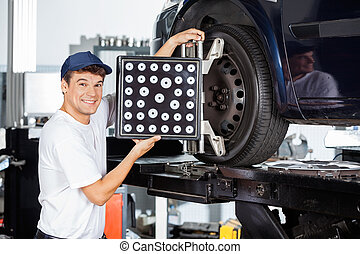 Mechanic Using Wheel Aligner On Car