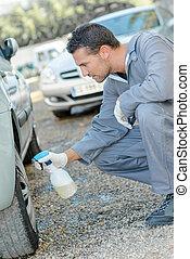 Mechanic washing a customer's car wheels