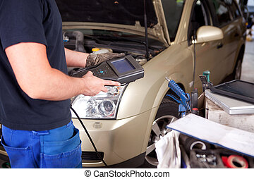 Mechanic with Diagnostic Equipment - Detail of a mechanic...