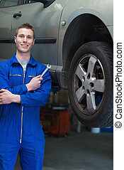 Mechanic with hand tool standing by car