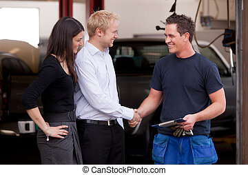 A happy attractive mechanic shaking hands with a customer couple, happy with their service