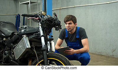 Mechanic with tablet tries to repair a motorcycle in car service