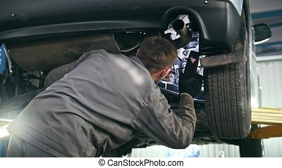 Mechanic with the lamp is checking the bottom of car in...