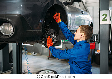 Mechanic with wrench repairs the suspension of car