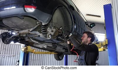 Mechanic worker man grind rusty bolts with electric grinder tool near lifted car