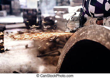 mechanic worker using grinder for polishing an iron block