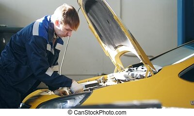 Mechanic working in the open hood of the car - the engine, the battery, the injector - automotive service