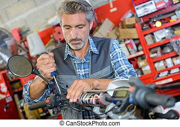 Mechanic working on handlebars of scooter