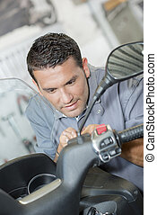 Mechanic working  on scooter