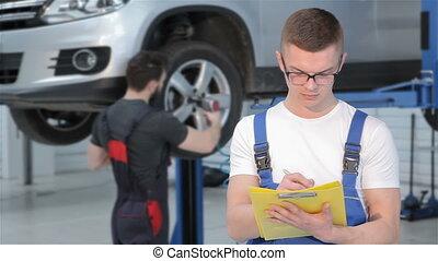 Mechanic writes down something to the yellow log book