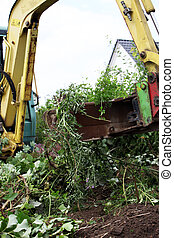 Mechanical digger clearing a building plot of overgrown plants and vegetation