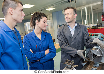 mechanical engineer showing apprentice a machine