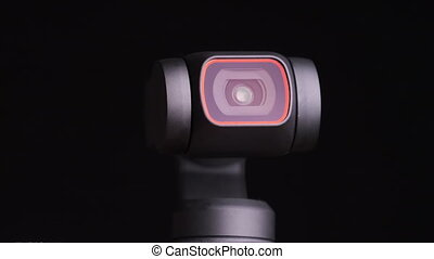Mechanical gimbal camera lens rotates on black background, close-up. The robotic camera rotates in different directions. Portable camera with image stabilization. Security and object tracking. Macro.
