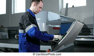 Mechanical technician programming punching the machine CNC....