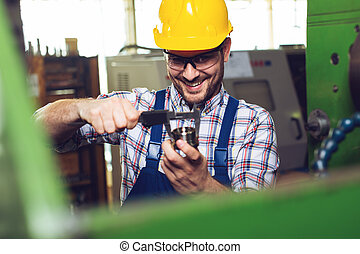 Mechanical technician worker hands measuring detail tool after processing at workshop with sliding caliper -