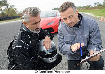 mechanician and pilot standing near a race car on track