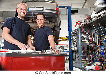 Mechanics at an auto shop - Two happy mechanics standing in...