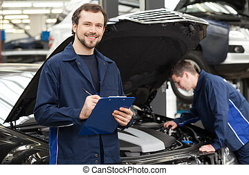 Mechanics at repair shop. Cheerful young mechanic writing something in his clipboard while another one fixing a car on the background