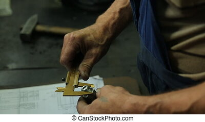 Mechanics hand, checks the item after the repair. workshop for car repairs or a large factory where he works.