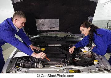Mechanics looking at a car engine