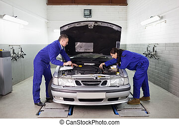 Mechanics looking at the engine in a garage