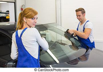 Mechanics or glaziers install windshield or windscreen on car