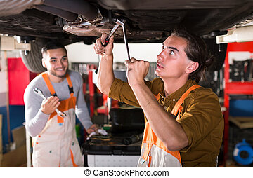 Mechanics repairing exhaust system