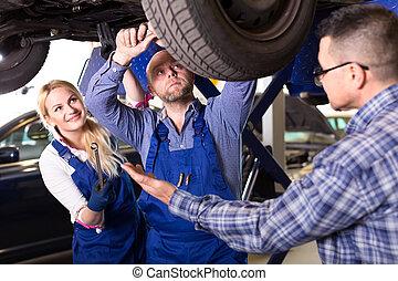 Mechanics repairing suspension - Driver has brought his car...