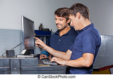 Mechanics Using Computer In Garage - Male mechanics using...