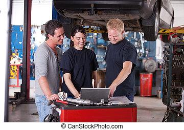 Mechanics Using Laptop - Team of mechanics looking at a...